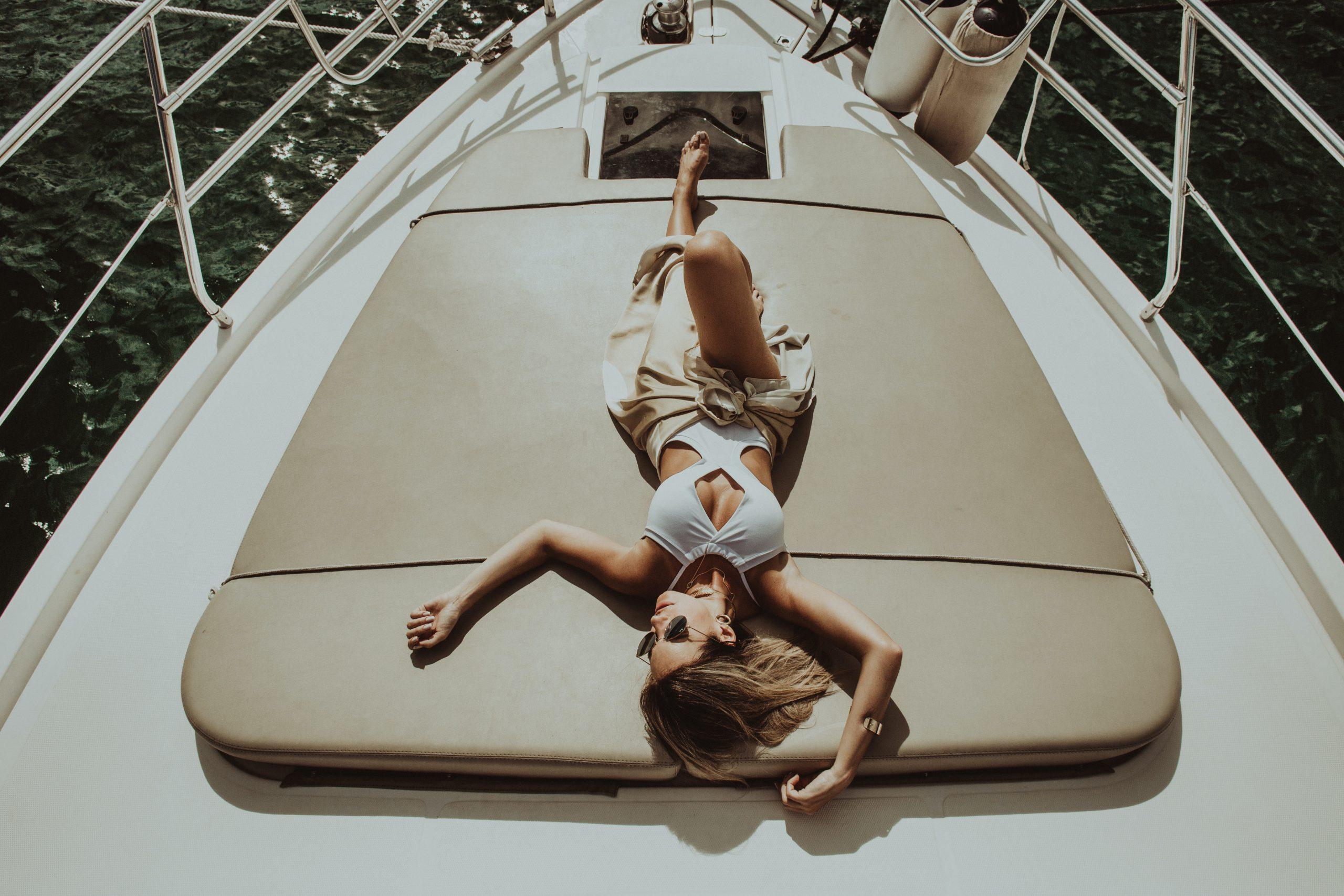 woman lying on gray mat on white boat